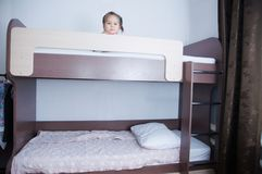Bunk bed in child room. little girl alone lying on bed. chocolate shade in the interior with white walls. Brown furniture for children domestic room stock images