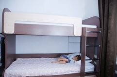 Bunk bed in child room. little girl alone lying on bed. chocolate shade in the interior with white walls. Brown furniture for children domestic room stock photo