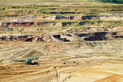 Bunk wall surface mine with exposed colored minerals and brown coal, the pit mining equipment Royalty Free Stock Photography