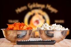 Bunkar av popcorn- och chipschiper med TVfjärrkontrollen royaltyfri fotografi
