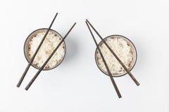 Bunkar av smakliga ris med pinnar som isoleras på vit Arkivfoton
