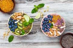 Bunkar för smoothies för superfoods för frukost Acai och för matcha för grönt te som överträffas med chia-, lin- och pumpafrö, bi arkivfoton