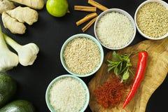 Bunkar med olika typer av ris, grönsaker och kryddor Arkivfoto