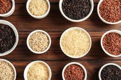 Bunkar med olika typer av ris på träbakgrund royaltyfria foton