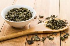 Bunkar med torrt grönt te, spridda blad på tabellen Royaltyfri Fotografi