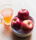 Bunke av äpplen och exponeringsglas av fruktsaft Fotografering för Bildbyråer