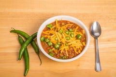 Bunke av chili med ost och skivade peppar Arkivfoto