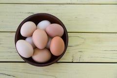 Bunke av fria ägg för bur på den gula tabellen royaltyfri fotografi