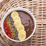 Bunke av frukosten med pollen för bi för chokladbanan smoothies garnerat, chiafrö, gojibär och på trä Royaltyfri Foto