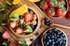 Bunke av Granola med nya frukter på trätabellen royaltyfria foton