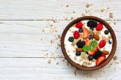 Bunke av grekisk yoghurt med granola, havre, bär och muttrar för sund frukost royaltyfri foto