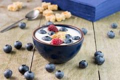 Bunke av hela blåbär i den vita yoghurten på den lantliga trätabellen royaltyfri foto
