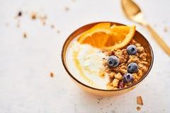 Bunke av hemlagad granola med yoghurt, honung, nya orange och djupfrysta blåbär royaltyfri foto