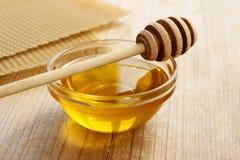 Bunke av honung och honungskakan i bakgrunden Royaltyfri Bild
