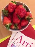 Bunke av jordgubbar och tidskrifter Royaltyfria Bilder
