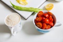 bunke av körsbärsröda tomater och en kopp av ris Royaltyfri Fotografi