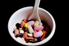 Bunke av kapslar för medicinpreventivpillerminnestavlor i svart bakgrund royaltyfria bilder