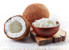 Bunke av kokosnötolja och nya kokosnötter Royaltyfria Bilder