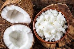 Bunke av kokosnötolja och nya kokosnötter Arkivfoton