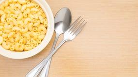 Bunke av lagad mat makaronipasta med gaffeln och skeden på den wood tabellen Arkivfoton