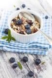 Bunke av mysli med nya blåbär på den vita trätabellen Royaltyfria Foton