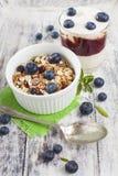 Bunke av mysli med nytt blåbär och exponeringsglas av yoghurt på whi Arkivfoton