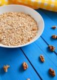 Bunke av nya havremjölvalnötter på mat för tabell för kricka lantlig varm och sund, för frukost Arkivbilder