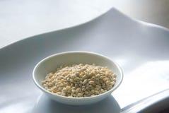 Bunke av organiskt pärlemorfärg korn på den vita plattan Arkivfoto