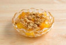 Bunke av persikor med farin och havre på den wood tabellen Royaltyfria Bilder