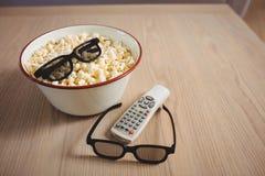 Bunke av popcorn, exponeringsglas 3D och televisionfjärrkontrollen på tabellen Arkivfoto