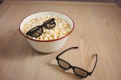 Bunke av popcorn och exponeringsglas 3D på tabellen Royaltyfria Bilder