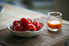 Bunke av röda tomater och exponeringsglas av morotfruktsaft på tabellen Arkivbild