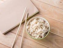 Bunke av ris med träpinnar på tabellen. Royaltyfri Bild