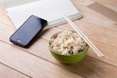 Bunke av ris med träpinnar på tabellen. Arkivfoton