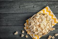 Bunke av smakligt popcorn på träbakgrund, bästa sikt arkivfoto