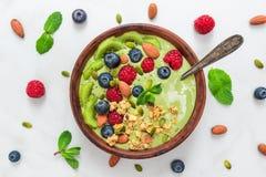 Bunke av smoothien för grönt te för matcha med ny bär, muttrar, frö och havregranola med en sked för sund frukost fotografering för bildbyråer