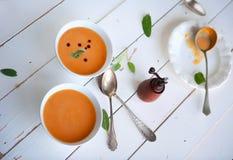 Bunke av soppa med pumpa på den vita trätabellen arkivfoton