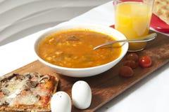 Bunke av soppawithSquarepizza på den wood tabellen Royaltyfri Foto