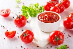 Bunke av tomatsås och körsbärsröda tomater på trätabellen royaltyfria bilder
