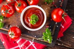 Bunke av tomatsås och körsbärsröda tomater på trätabellen arkivfoto