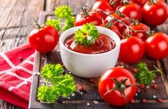 Bunke av tomatsås och körsbärsröda tomater på trätabellen royaltyfri foto
