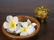 Bunke av tropiska blommor och guld- färgware Royaltyfri Foto