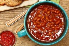 Bunke av vita bönor i tomatsås och ketchup på tabellen Arkivfoto