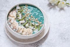 Bunke för smoothie för frukostspirulinakokosnöt som överträffas med kokosnötflingor och bär Arkivfoton