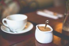 Bunke för vitt socker för närbild med farin på en vit kopp med ett tefat på tabellen royaltyfri fotografi