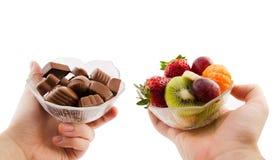 Bunke med choklader och en bunke av frukt Arkivbilder
