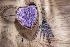 Bunke med den salta gruppen för crystal hav av parfymerad lavendel på den wood boaen arkivfoton