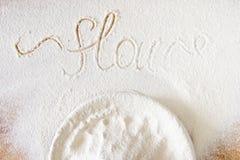 Bunke med mjöl på trätextur Ordmjöl som är skriftligt från handen arkivbilder