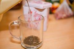 Bunke med Tea Häll vatten i te ny tea Arkivbild