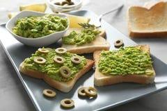 Bunke och läckra rostade bröd med avokadot och oliv Royaltyfri Bild